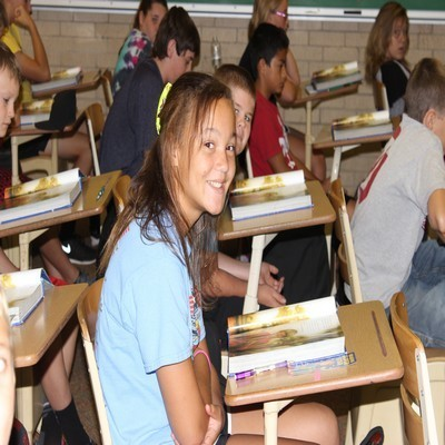 Upper Elementary students in class, facing toward the right edge. Books open on each wooden, single-piece desk. One student, centered, female, with her head turned toward the camera and smiling.